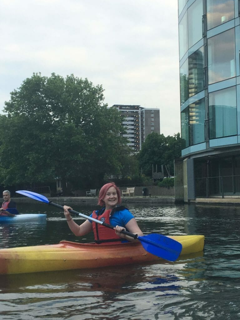 Katie posing for a picture in her kayak with paddle raised