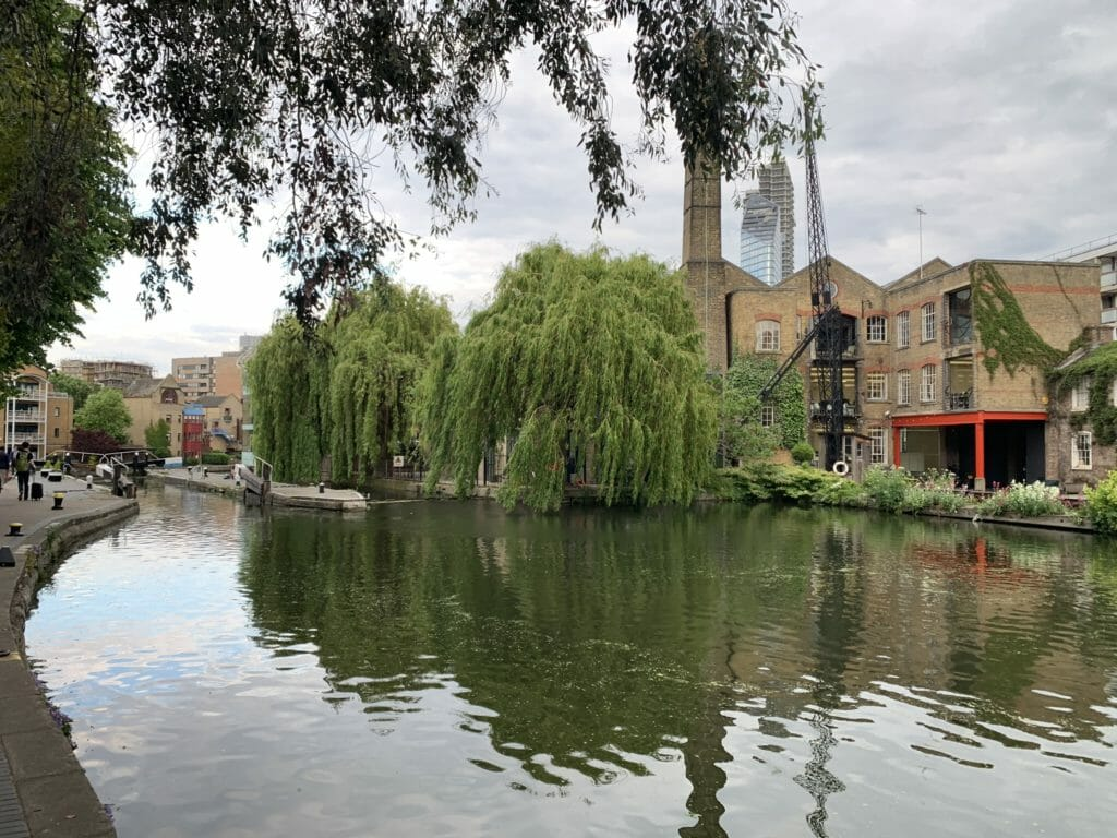 A turning pond in the canal with weeping willows and industrial buildings in the background