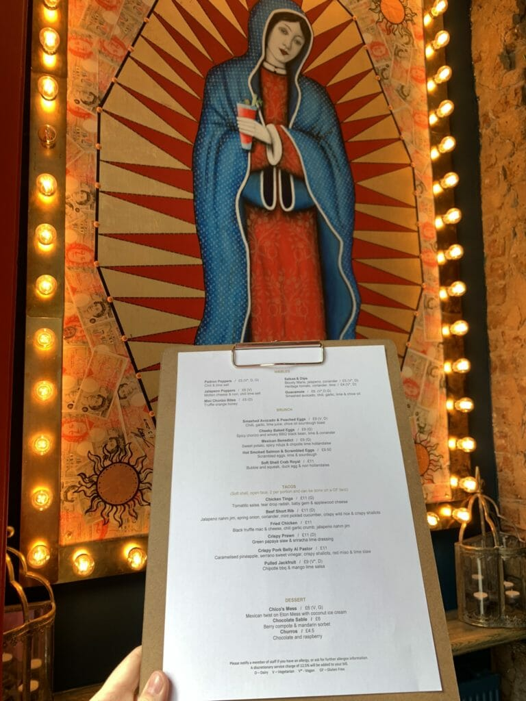 Menu on a clipboard in front of the Madonna picture