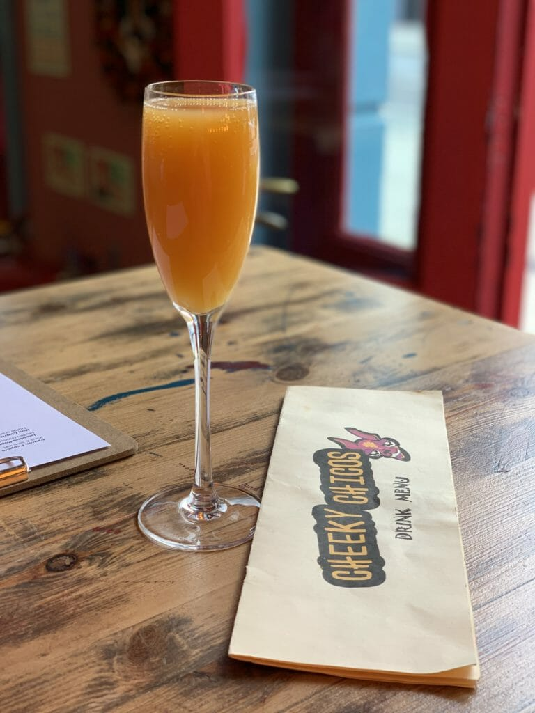 Glass of mimosa and menu on the table