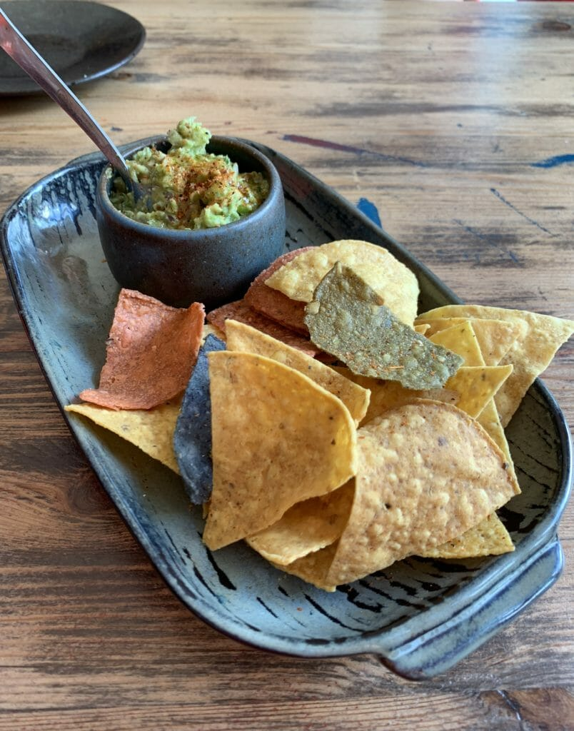 Guacamole avocado dip with different coloured corn tortilla chips