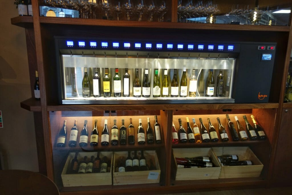 Enomatic machine above the wine shelves with bottles available by the glass