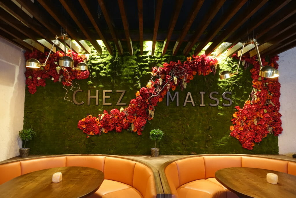 Wall covered with greenery and flowers behind the booths in Chez Maiss