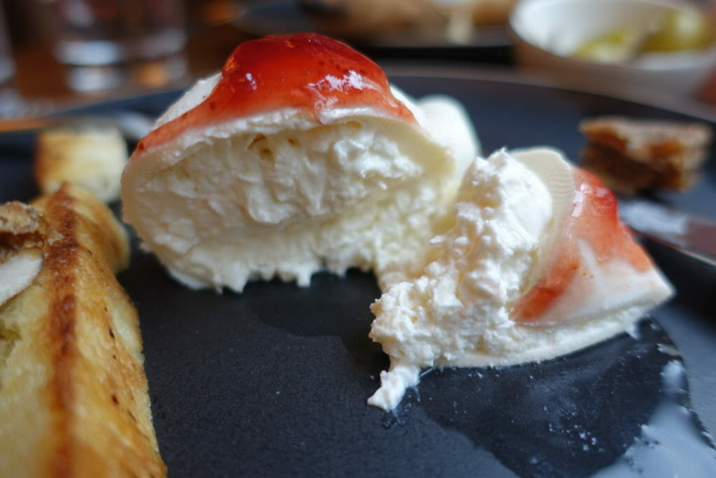 Close up of the cut open burrata with jam on top