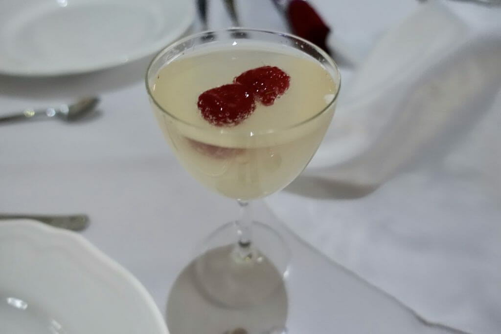 Cocktail with raspberries floating in it