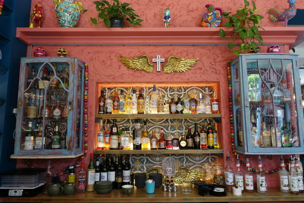 Back bar lit up with lots of Mexicana decorations and a salmon pink wall