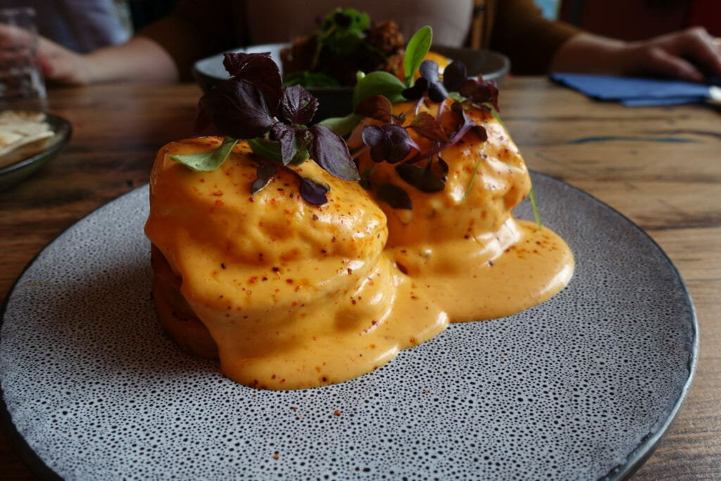 Two eggs Benedict stacks covered with chipotle hollandaise with micro herbs on top