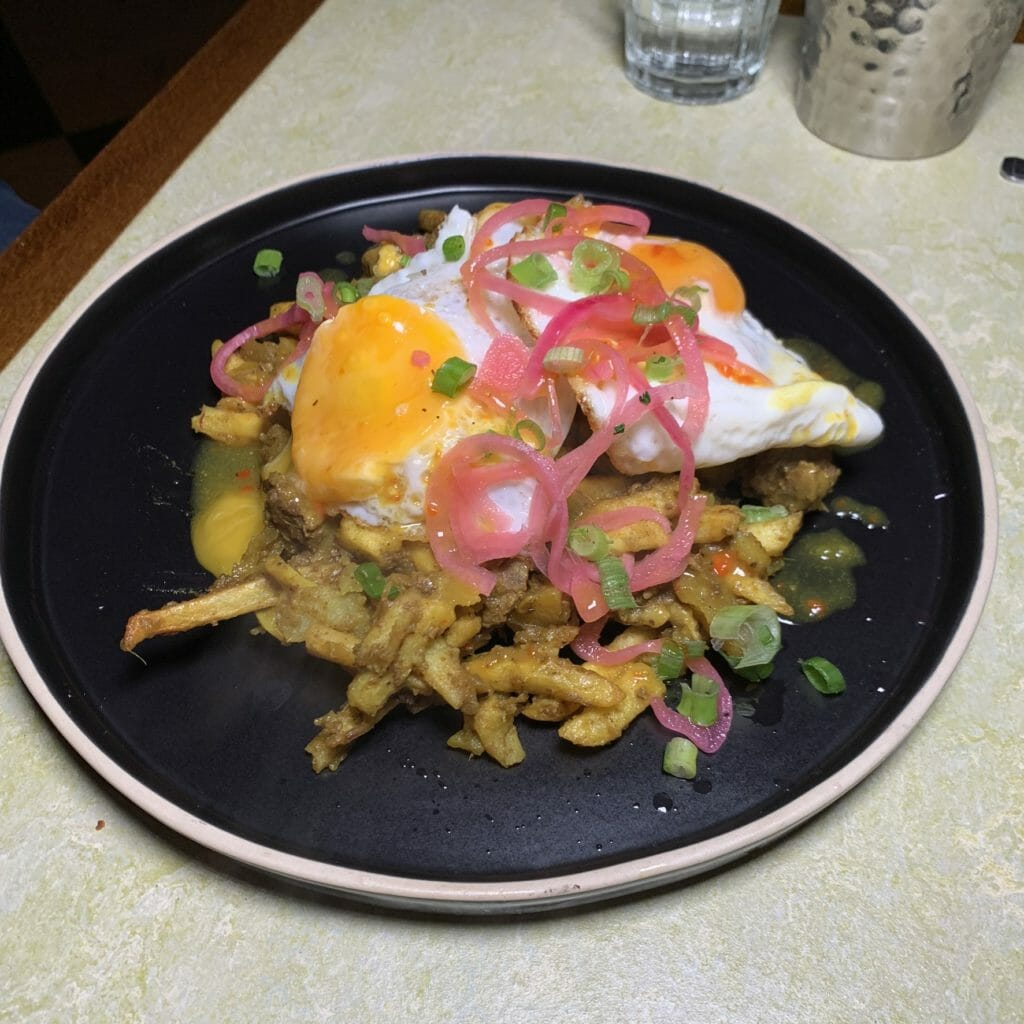 Curry goat hash with potato and fried eggs