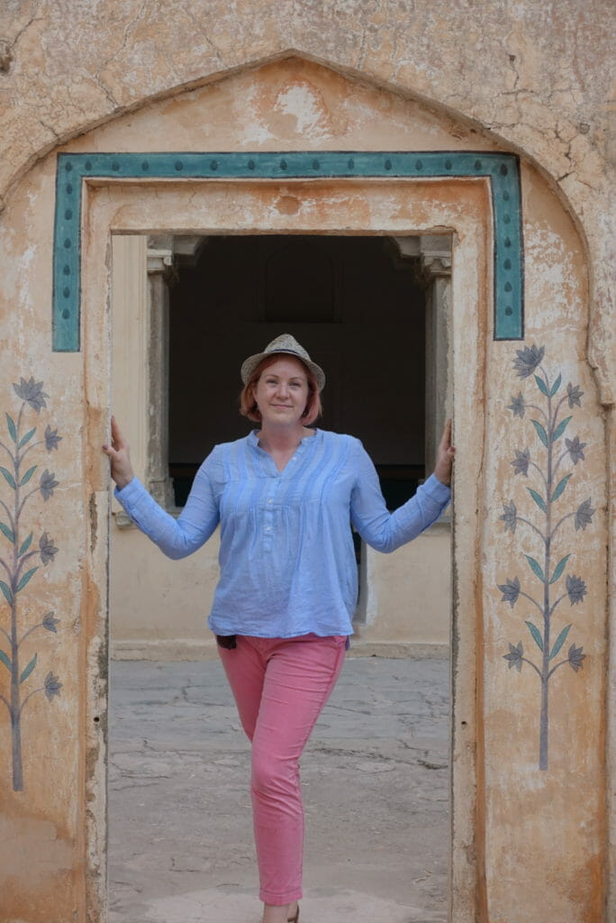 Katie in pink trousers, blue cotton top and hat in another doorway