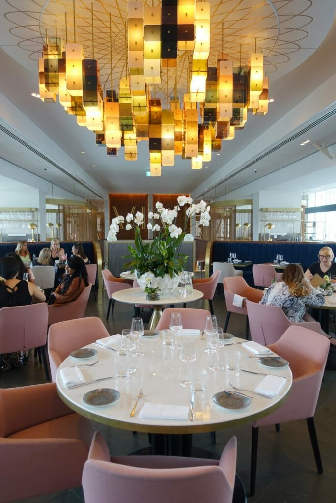 The main part of the restaurant with dusky pink chairs, round tables and a great central light fitting