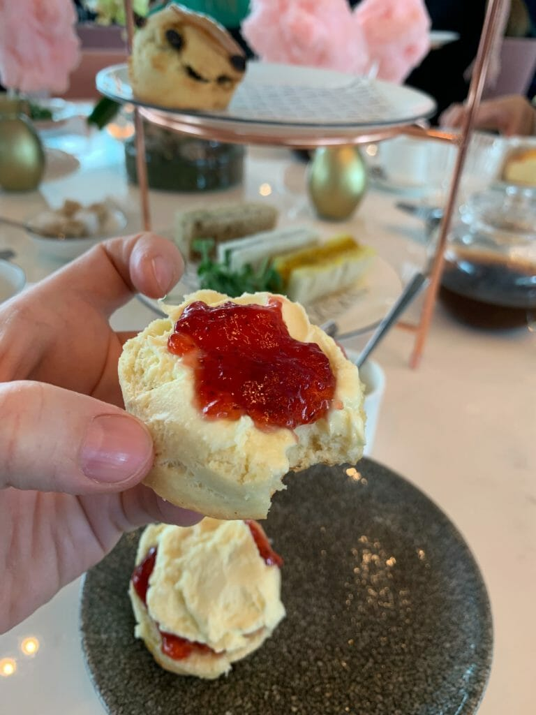 Partially eaten scone with jam and cream