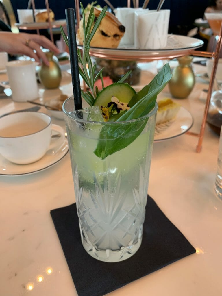 Weeping guitar cocktail garnished with herbs and cucumber