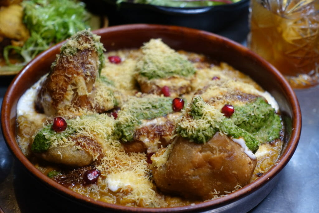 Hot mixed chaat dish with chutneys drizzled on top