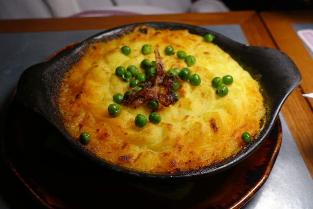 Dish of shepherds pie with mash and peas on top