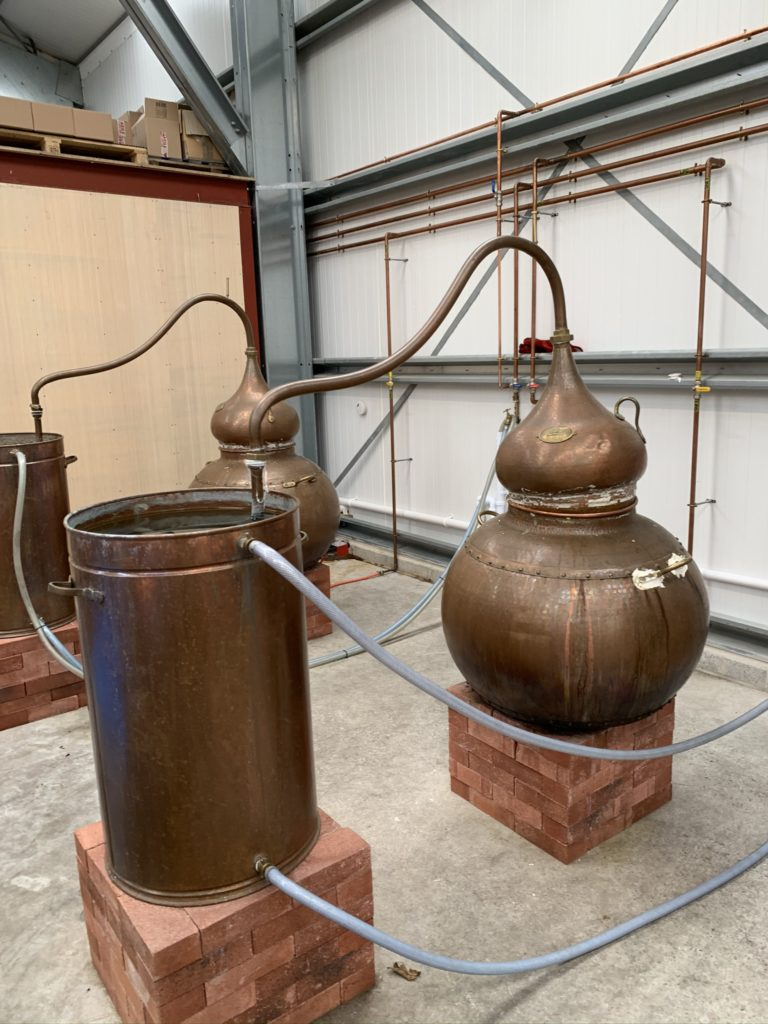 The copper gin stills sitting on bricks covering the paella cooking rings