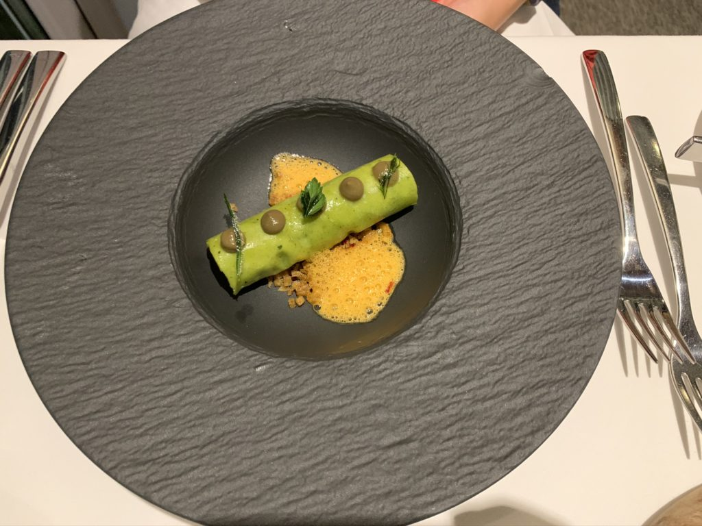 Black dish with green cannelloni and orange bisque in the middle