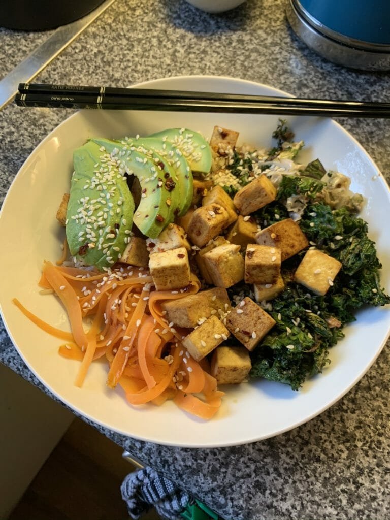 Bowl of bibimbap with tofu, avocado veggies with chopsticks