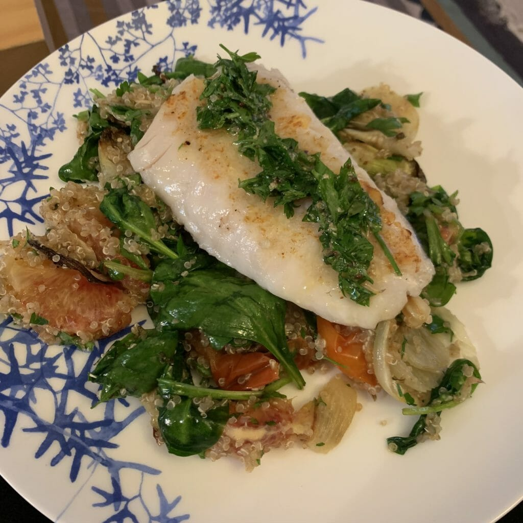 White fish on top of a quinoa salad with a herb sauce