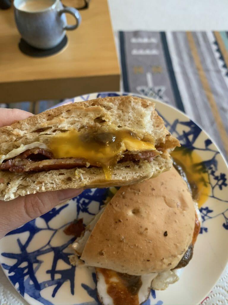 Side shot of the bacon sandwich cut in half with runny egg yolk