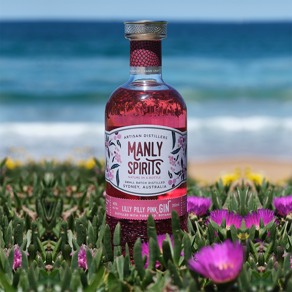 Manly bottle with pink flowers and succulent plants by the beach