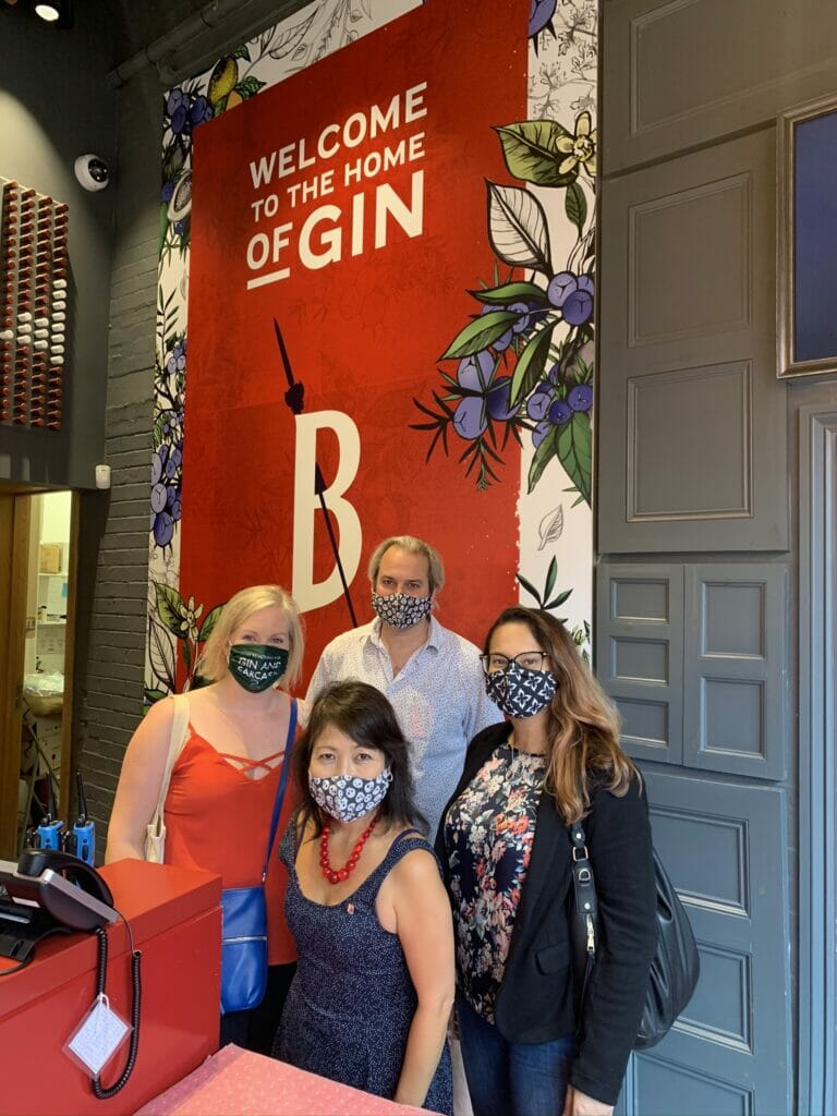 Posing with facemasks in front of the Beefeater sign in the shop