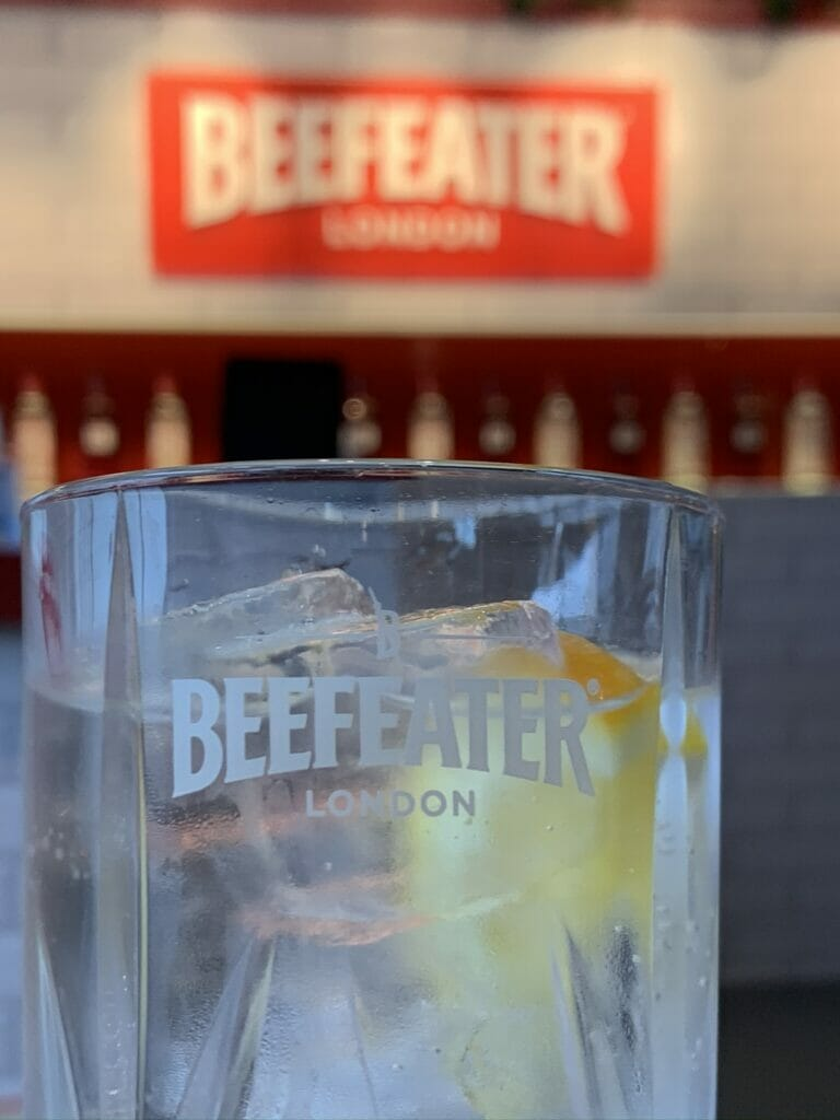 Beefeater gin and tonic in a branded Beefeater glass in front of the sign in the bar
