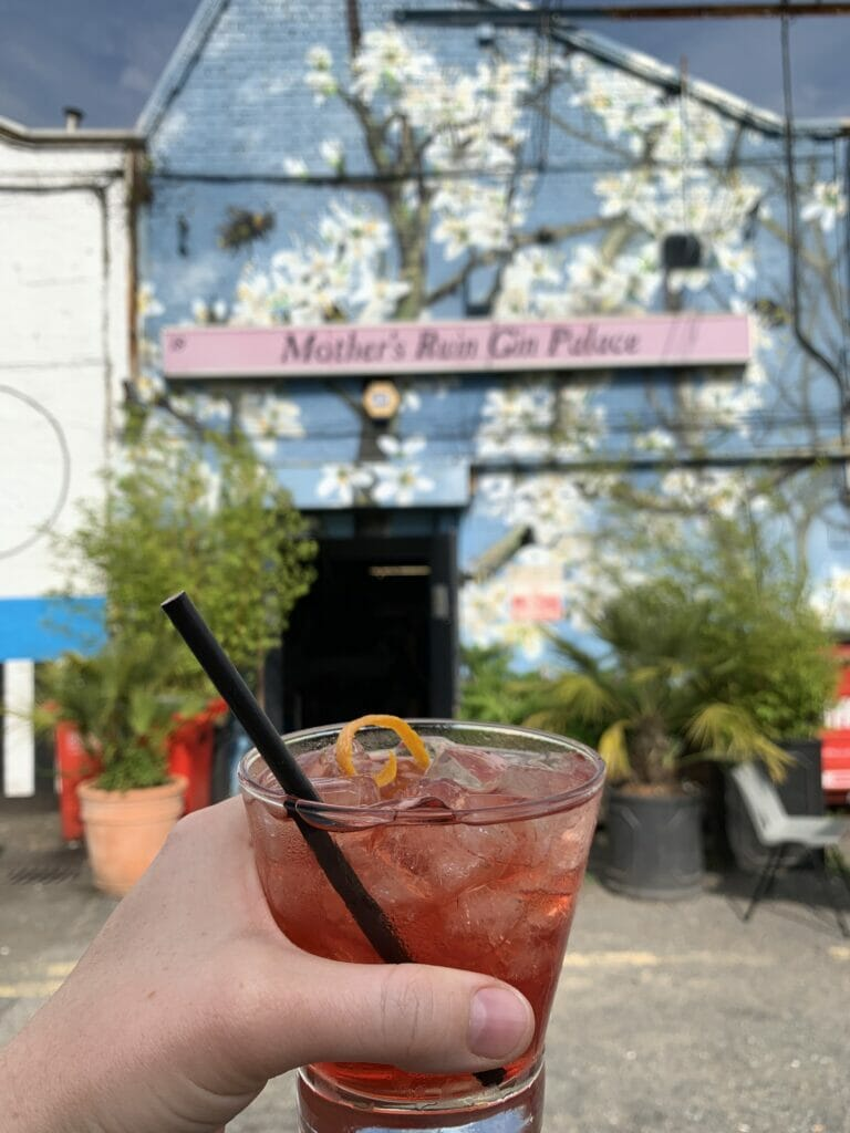 Mother's Ruin negroni in front of the distillery frontage painted with white blossom