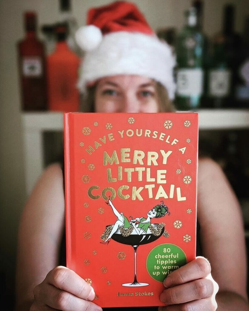 Have yourself a Merry Little Christmas cocktail book held by Emma Stokes