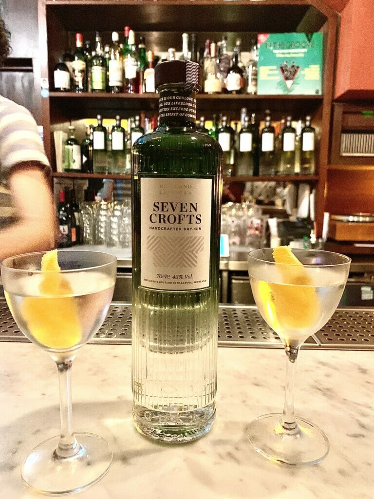 Seven Crofts gin bottle on a bar with two martini glasses