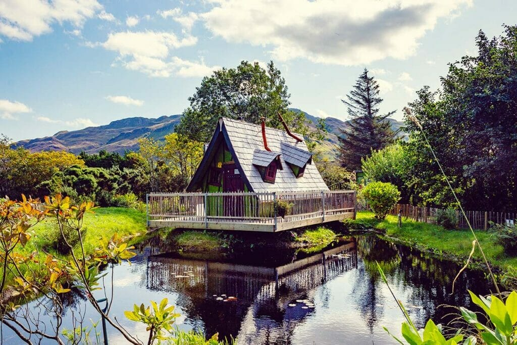 The Fairy Tale Distillery on a pond surrounded by green with mountains in the background