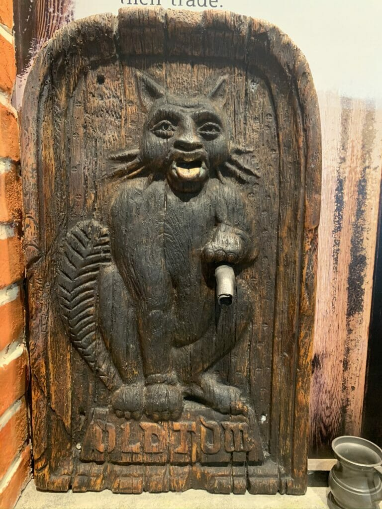 Wooden caving of a black cat with gin tube coming out of its paw