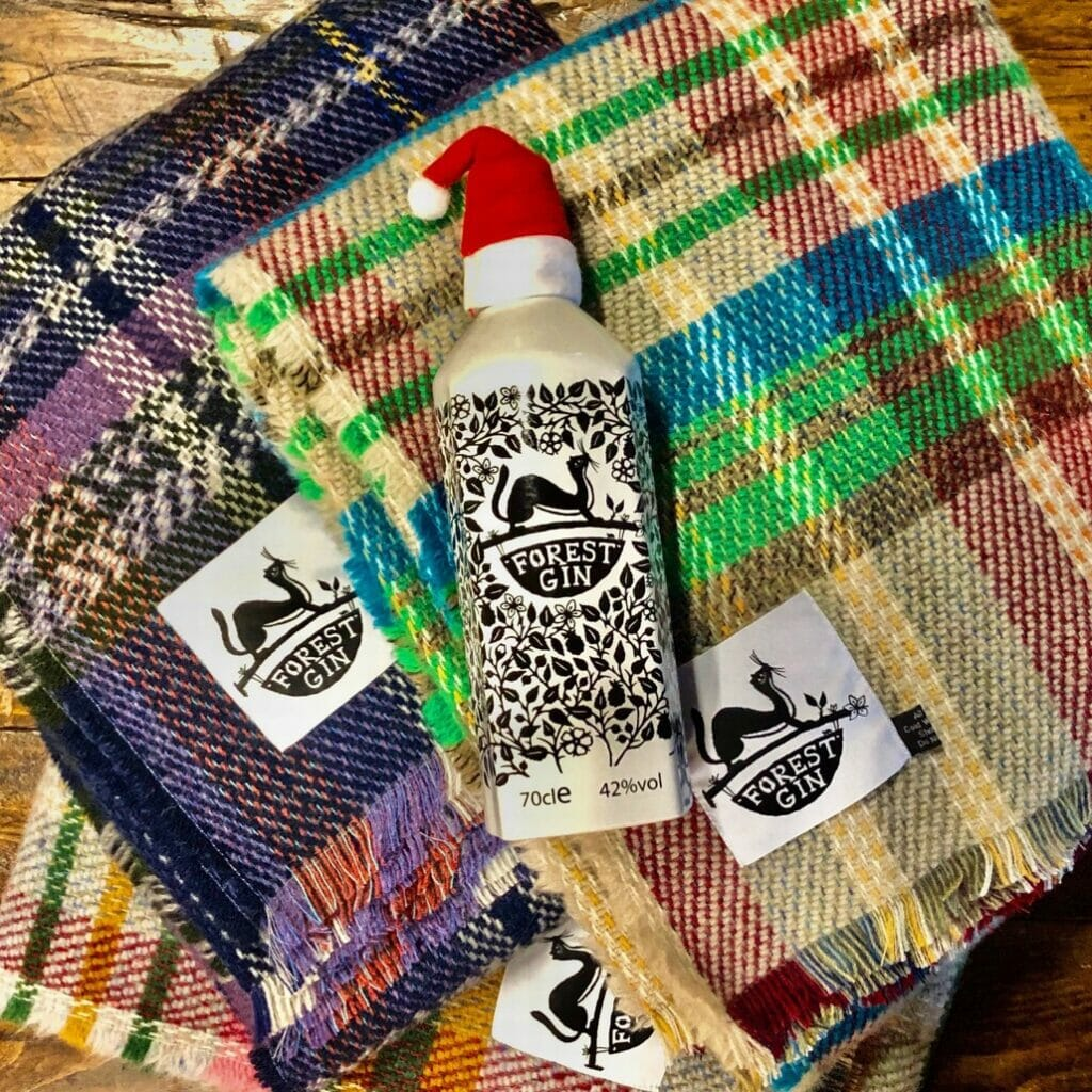 Forest gin bottle with a mini Santa hat on top of the gin blankets