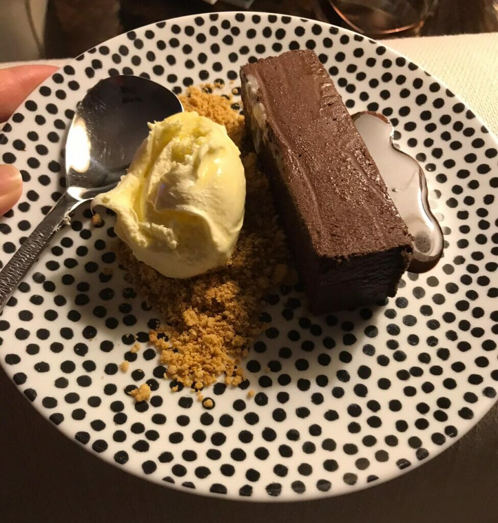 Chocolate Pave with clotted cream, chocolate sauce and cystallised peanutes on spotty plate