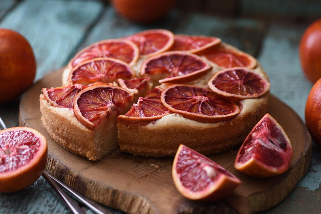 Blood orange slices on cake served on oak board closeup