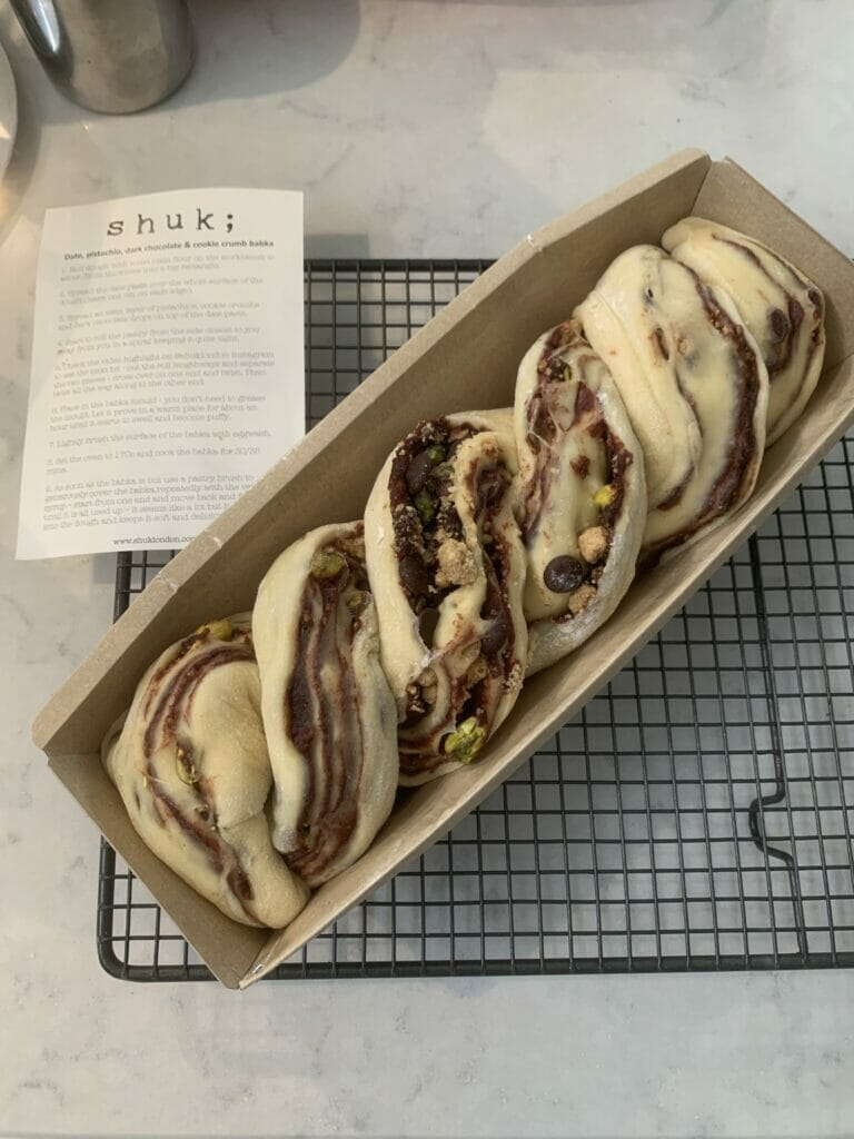 Uncooked plaited babka dough in the mould on a cooling rack, ready for the oven
