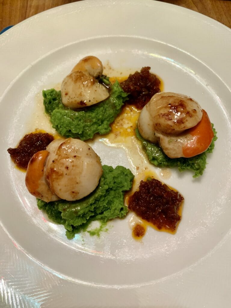 Three scallops plated on top of green pea puree with blobs of red chorizo jam